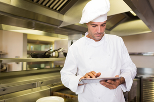 Male cook using digital tablet in kitchenの写真素材 [FYI00000489]