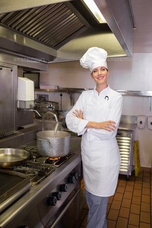 Smiling female cook with arms crossed in kitchenの写真素材 [FYI00000495]