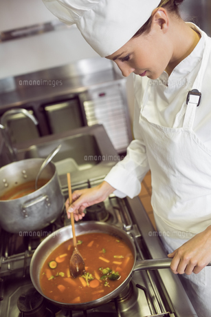 Concentrated female cook preparing food in kitchenの写真素材 [FYI00000500]