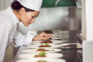 Concentrated female chef garnishing food in kitchenの写真素材 [FYI00000502]