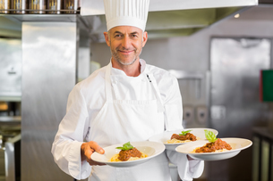 Confident male chef with cooked food in kitchenの写真素材 [FYI00000505]