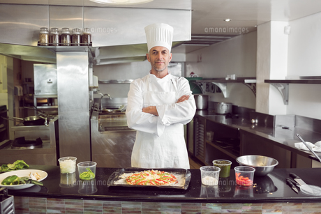 Confident male chef with cooked food in kitchenの写真素材 [FYI00000506]