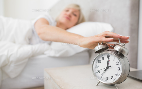Woman extending hand to alarm clock in bedの写真素材 [FYI00000507]