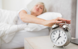 Woman extending hand to alarm clock in bedの写真素材 [FYI00000507]