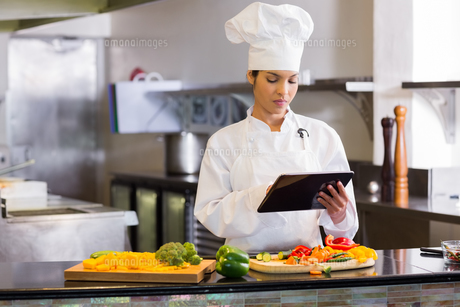 Female chef using digital tablet while cutting vegetablesの写真素材 [FYI00000509]