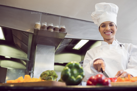 Smiling female chef cutting vegetables in kitchenの写真素材 [FYI00000510]