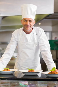 Confident male chef with cooked food in kitchenの写真素材 [FYI00000511]
