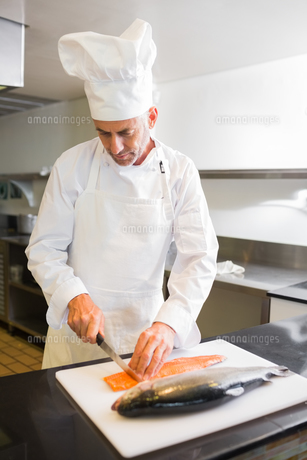 Concentrated male chef cutting fish in kitchenの素材 [FYI00000513]