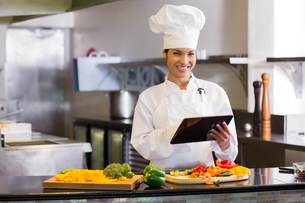 Smiling chef using digital tablet while cutting vegetablesの写真素材 [FYI00000514]