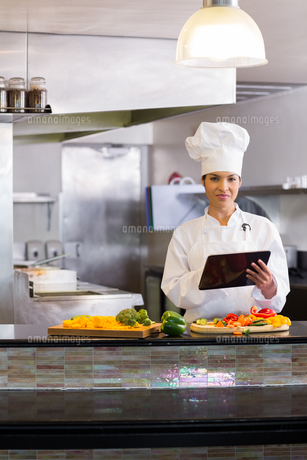 Female chef using digital tablet while cutting vegetables in kitchenの写真素材 [FYI00000515]
