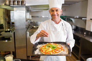 Confident male chef holding cooked food in kitchenの写真素材 [FYI00000517]