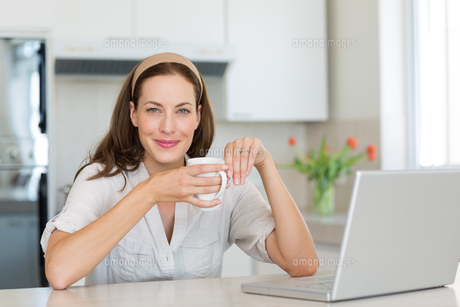 Smiling woman with coffee cup and laptop in kitchenの素材 [FYI00000523]