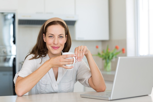 Smiling woman with coffee cup and laptop in kitchenの写真素材 [FYI00000523]