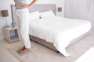 Low section of a woman standing on scale in bedroomの写真素材 [FYI00000525]