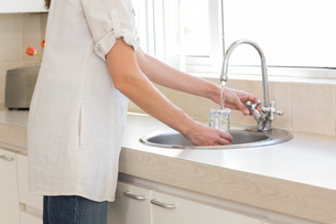 Mid section of a woman washing glass at washbasin in kitchenの写真素材 [FYI00000529]