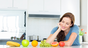 Smiling woman with fruits on counter in kitchenの写真素材 [FYI00000530]