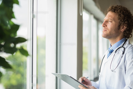 Thoughtful doctor with clipboardの写真素材 [FYI00000546]
