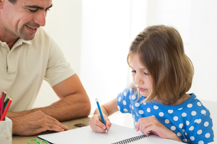 Father looking at daughter coloringの写真素材 [FYI00000561]
