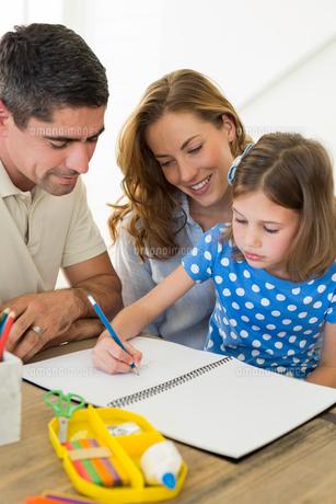 Parents assisting daughter in coloringの写真素材 [FYI00000567]