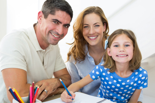 Parents assisting daughter in coloring at homeの写真素材 [FYI00000571]