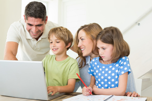 Family using laptop at tableの写真素材 [FYI00000576]