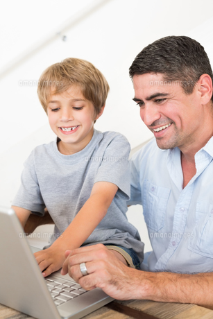 Father reaching son to use laptopの写真素材 [FYI00000580]