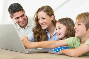 Smiling family using laptopの写真素材 [FYI00000581]