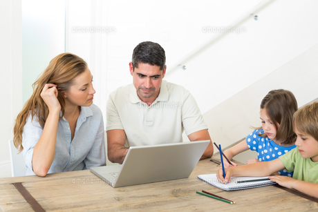 Parents using laptop while children coloringの写真素材 [FYI00000582]