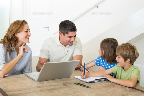 Parents with laptop assisting children coloringの写真素材 [FYI00000583]