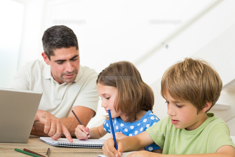 Father with laptop assisting children drawingの写真素材 [FYI00000584]