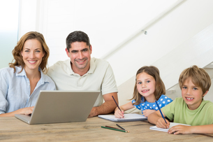 Parents with laptop while children coloring at tableの写真素材 [FYI00000585]
