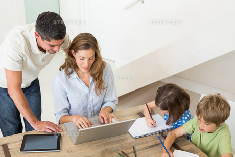 Parents using laptop while children coloring at homeの写真素材 [FYI00000590]