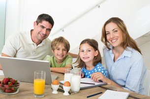 Portrait of family using laptop while having breakfastの写真素材 [FYI00000594]