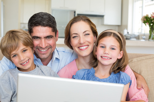 Smiling family with laptop in houseの写真素材 [FYI00000595]
