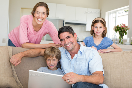 Smiling family using laptop in sitting roomの写真素材 [FYI00000599]