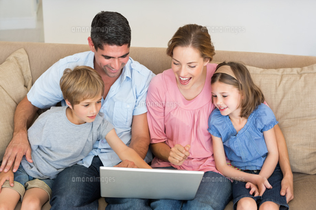 Family using laptop together on sofaの写真素材 [FYI00000602]