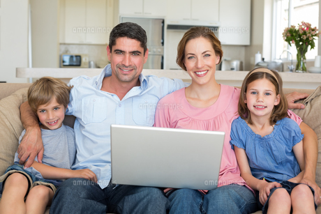 Family with laptop sitting on sofaの写真素材 [FYI00000603]