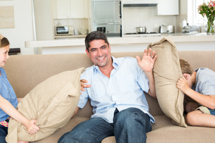 Family having cushion fight on sofaの素材 [FYI00000604]