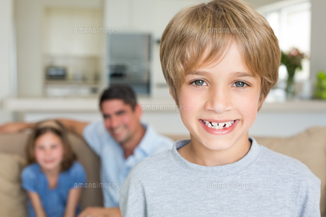 Boy smiling with family in backgroundの写真素材 [FYI00000605]