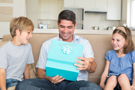 Father opening gift given by children on sofaの素材 [FYI00000606]