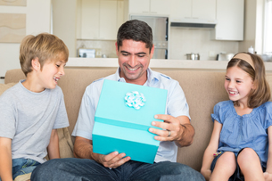 Father opening gift given by children on sofaの写真素材 [FYI00000606]