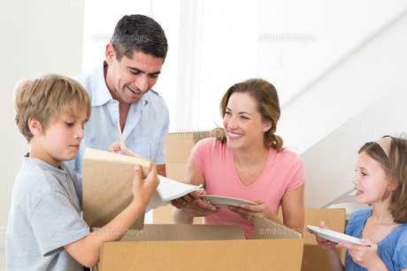 Family unpacking cardboard box in houseの写真素材 [FYI00000610]
