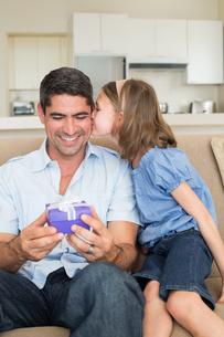 Girl kissing father holding gift box on sofaの写真素材 [FYI00000612]