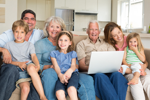 Cheerful family with laptop in living roomの写真素材 [FYI00000617]