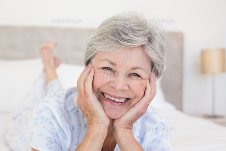 Senior woman with head in hands on bedの写真素材 [FYI00000622]