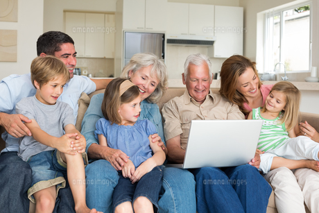 Multigeneration family using laptop in living roomの写真素材 [FYI00000623]