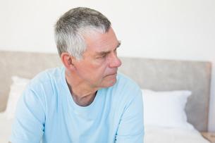 Senior man looking away on bedの写真素材 [FYI00000624]