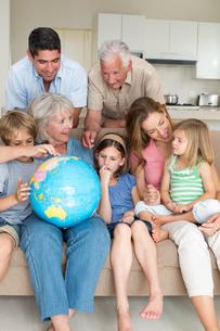 Family exploring globe in living roomの写真素材 [FYI00000628]
