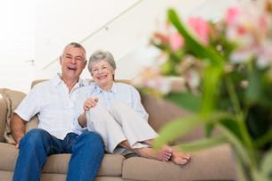 Happy senior couple relaxing on sofaの写真素材 [FYI00000629]