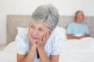 Sad senior woman with husband on bedの写真素材 [FYI00000632]